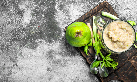 Smoothie with banana, pear and celery. On rustic background. 스톡 콘텐츠