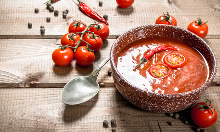 Tomato soup with spices and hot chili peppers. On a wooden background. 스톡 콘텐츠