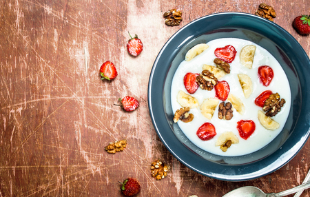 Semolina porridge with strawberries and nuts. On rustic background.