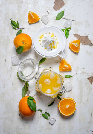 Fresh orange juice with ice, with slices of oranges and a juicer. On rustic background. Top view