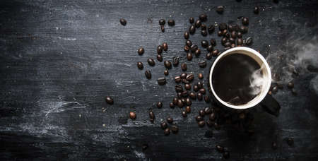 Fresh coffee and roasted grain . On black rustic background.