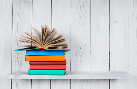 The open book on other multi-coloured books. On a wooden shelf. A wooden, white background.