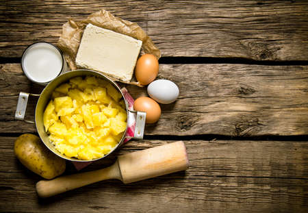 Potato food . Ingredients for mashed potatoes - eggs, milk, butter and potatoes on wooden background. Free space for text. Top view
