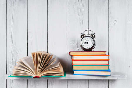 The open book, other multi-coloured books and alarm clock. On a wooden shelf.