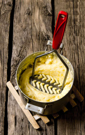 Potato food . Cooking mashed potatoes with pestle on wooden background.