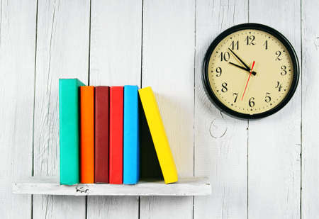 Watches and books on a wooden shelf. On a white, wooden background.
