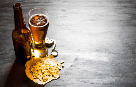 Beer background. Beer with peanuts on the black wooden table. Free space for text.