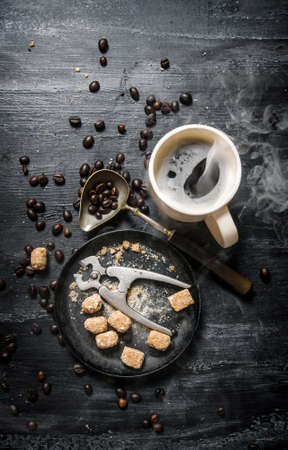 Fresh coffee. Coffee cup with brown sugar and roasted grains . On black rustic background.