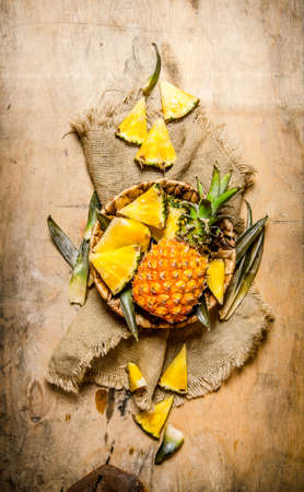 Fresh pineapples, whole and sliced in a basket on old fabric. On a wooden table. Top view