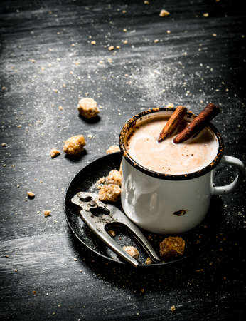Hot chocolate with cinnamon and cutters for sugar. On black rustic background.