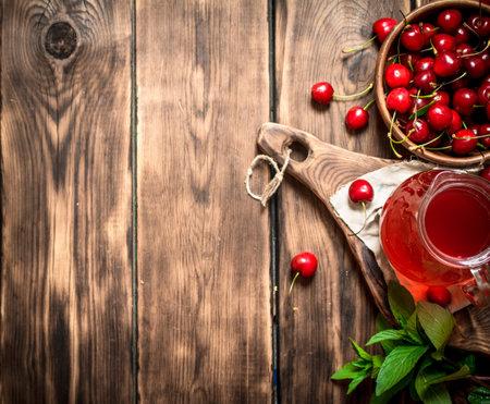 Fresh cherry juice . On a wooden background. Stock fotó
