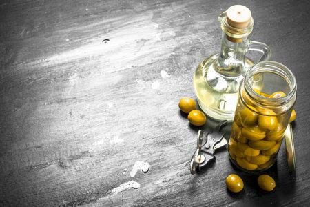 Olive oil in bottle. On the black chalkboard.