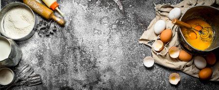 Baking background. Whisking eggs in the old bowl . On rustic background. Reklamní fotografie