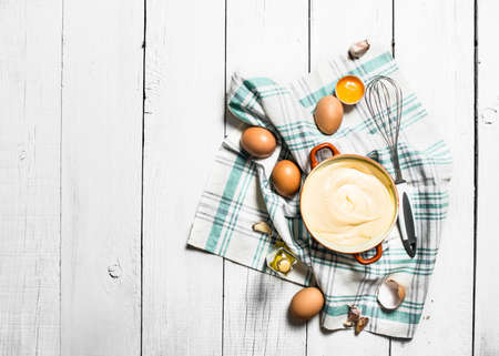 Fresh mayonnaise with the ingredients. On a white wooden background. Reklamní fotografie