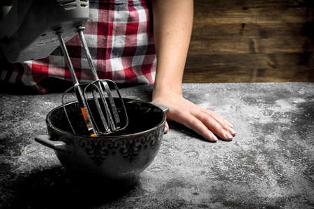 Dough background. A woman is preparing a fresh dough. On a rustic background.