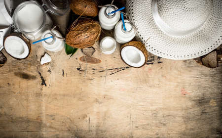Summer cocktail. Coconut milk in the bottles. On wooden background.