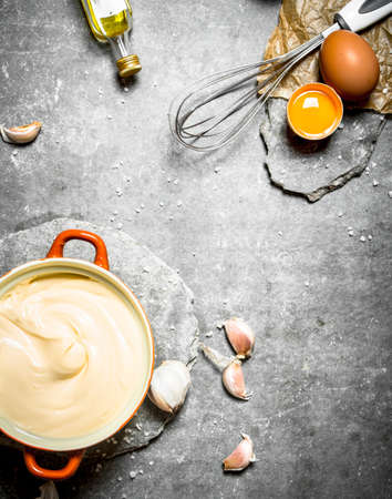 Fresh mayonnaise with the ingredients and whisk. On the stone table.