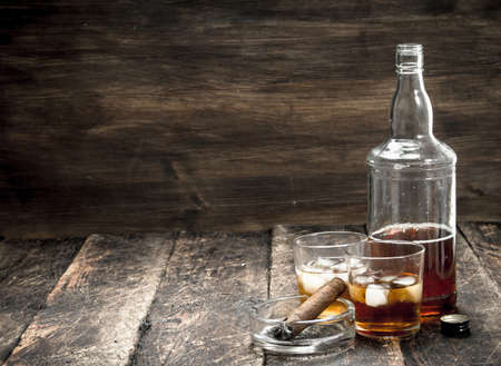 Whiskey with ice and a cigar. On a wooden background.