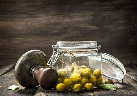 Marinated olives with seamer. On a wooden background.