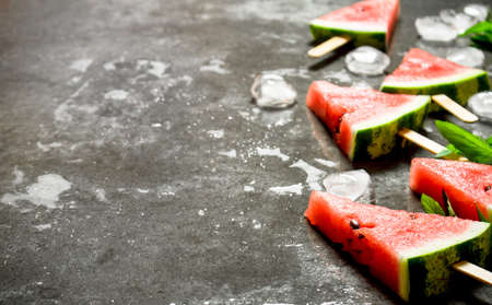 Watermelon ice cream on wooden sticks. On the stone table.
