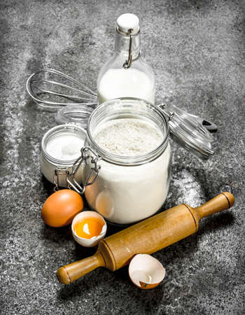 Baking background. Fresh ingredients for dough. On a rustic background.