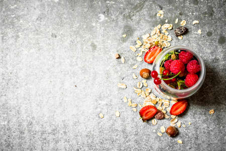 Fresh berries with muesli. On the stone table.
