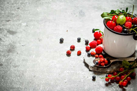 Fresh berries in a cup on a stone stand. On the stone table. 스톡 콘텐츠