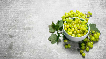 Green grapes in a bowl. On the stone table. 스톡 콘텐츠