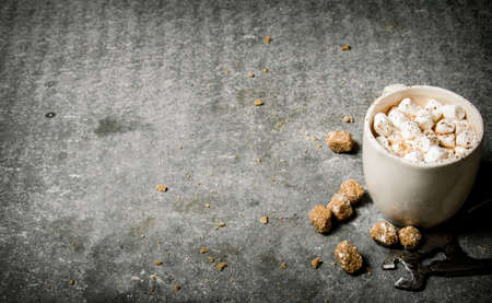 Hot chocolate with wire cutters and cane sugar. On a stone background.