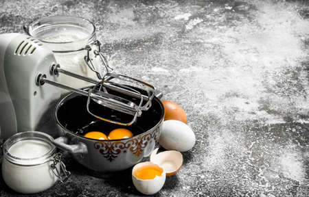 Baking background. Blend eggs with a mixer to make a dough. On a rustic background.