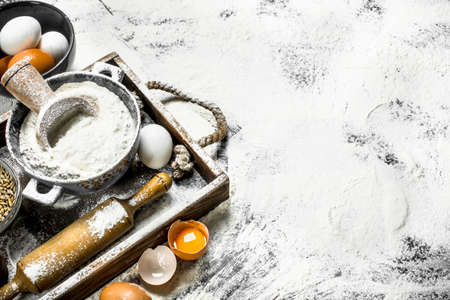 Dough backround. Flour with eggs and rolling pin. On the wooden box. Banque d'images