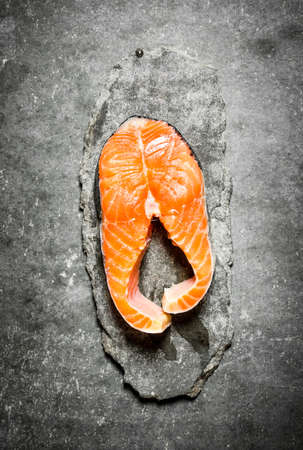piece of raw trout. On a stone background.