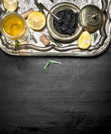 Black caviar with white wine on the old tray. On a black chalkboard.