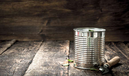 Food in tin can with opener. On a wooden background.