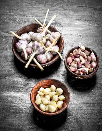 Fresh garlic in wooden bowls. On a black chalkboard. Reklamní fotografie