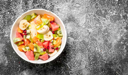 Tropical food . Fruit salad in a bowl. On rustic background.