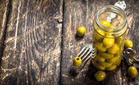 Pickled olives in glass jar. On a wooden background