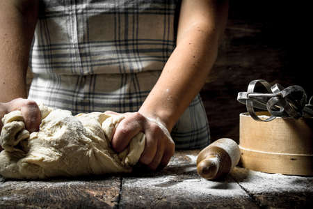 Dough background. Preparation of dough with tools. On a wooden table. Reklamní fotografie