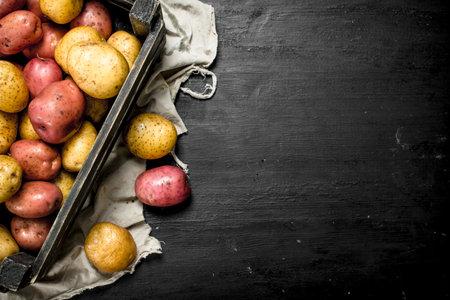 Fresh potatoes in an old box. On the black chalkboard.