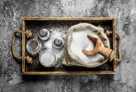 Salt in an old bag on a tray. On rustic background.