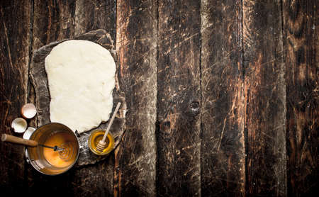 Dough background. The pastry ingredients. On a wooden table.