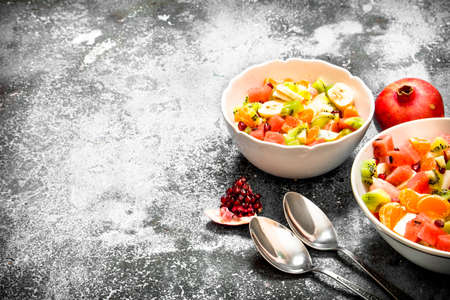 Tropical food . Fresh salad of fruits. On rustic background.