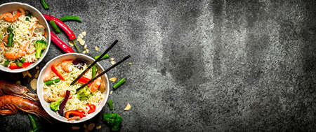 Asian food. Chinese noodles with vegetables and shrimp. On an old rustic background . 写真素材