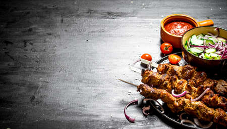 Shish kebab of pork and salad. On the black wooden table. Zdjęcie Seryjne