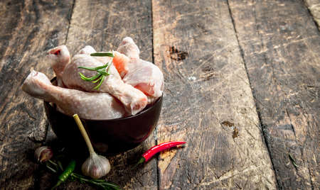 Raw chicken legs with garlic and spices in a bowl. On wooden background.