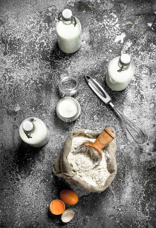 Baking background. Flour with fresh milk in bottles, sour cream and eggs. On a rustic background.