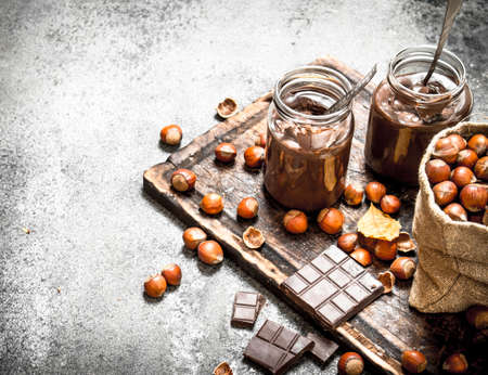 Chocolate butter with hazelnuts. On rustic background.