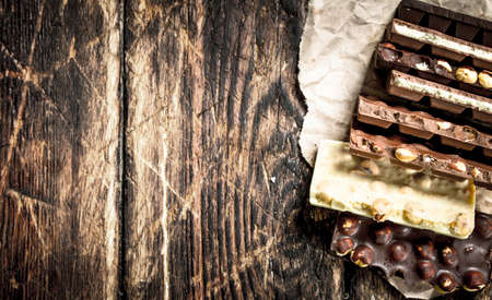 Different chocolate bars. On a wooden background. Standard-Bild