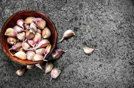 Peaces of fresh garlic in a wooden bowl. On a rustic background.