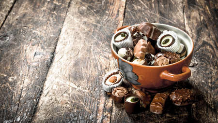 Chocolate candies in a bowl. On a wooden background.